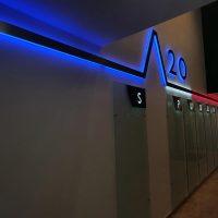 Stěna v interiéru, v horní části 3D černá čára přes celou stěnu, uprostřed výstupek tvaru obráceného písmena V a vpravo číslo 20, modré, bílé a červené podsvícení, pod čarou několik skleněných obdélníků postavených na výšku vpravo nahoře bíle prosvícené písmeno, v pozadí dveře, vpravo schody nahoru