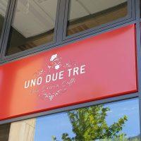 Červené panely montované v černých rámech mezi skleněnými okenními tabulkami, bílé logo UNO DUE TRE