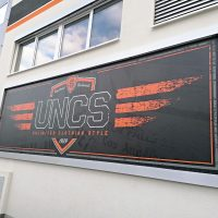 Světelný panel s dibondovým rámem, logo UNCS na černém podkladu, umístěno na zdi budovy