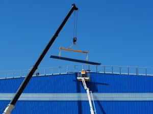 Rameno jeřábu zdvihá traverzu na střechu modré budovy, technik v reflexní vestě na plošině, modrá obloha