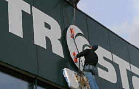 Technik provádí montáž 3D firemního loga Metrostav na fasádě administrační budovy
