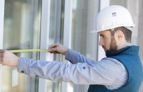 Mladý muž technik v ochranné přilbě provádí zaměření skleněné výplně