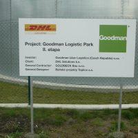 Obdélníková bílá reklamní cedule potištěná logy firem DHL a Goodman a informačními texty, instalovaná na kovových sloupech, stojící před plotem, v pozadí část kruhového objektu