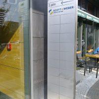 Stříbrný totem před vchodem do kancelářské budovy Budějovická alej B, orientační číslo 77, prosklené dveře, dlažební kostky
