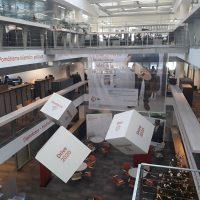 Tři bílé velké kostky s červenými nápisy, vzadu průhledný panel s nápisy a postavou držící skateboard, interiér s několika podlaží, průhled skrz budovu