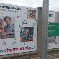 Dvě reklamní cedule z dibond desky umístěné mezi betonovými sloupy plotu, v popředí kovový sloup lampy, v pozadí obloha s mraky