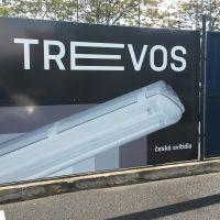 Reklama svítidel TREVOS na UV laminované kompozitní desce připevněné mezi dvěma sloupky na oplocení, v pozadí stromy