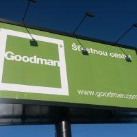 Pohled zespodu na dvojitý reklamní billboard firmy Goodman, zelenobíle potištěná dibond deska, černý rám a sloup, troje světla instalovaná na vrchu