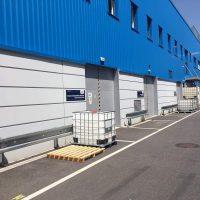 Šedo-modrá oplechovaná průmyslová budova, asfaltové prostranství, troje šedá vrata označená modrou cedulí lepenou na stěnu