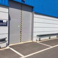Šedo-modrá oplechovaná průmyslová budova, šedá vrata označená modrou cedulí s bílým nápisem NEUTRALIZAČNÍ STANICE, svodidla