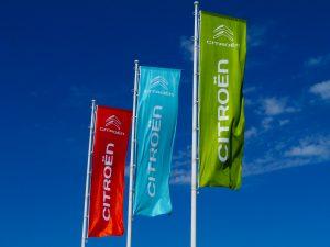 Tři barevné vlajky s bílým logem a názvem firmy Citroen, bílé stožáry, na pozadí modré nebe s mráčky