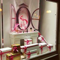 Výloha s bílými a zlatými dárky a bílým stolečkem, na kterém jsou umístěny parfémy, nad stolečkem je oválné otevřené okno tmavší růžové barvy s obrázkem Eifellovy věže uvnitř. Bílé pozadí