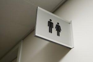 Skleněná navigační výstrč s černými piktogramy panáčků WC muži a ženy na bílé stěně