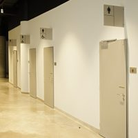 Řada šedých dveří, reklamní výstrče s piktogramy toalet páni, dámy, invalidé, béžová podlaha, bílá zeď, O2 Universum