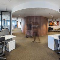 Fototapeta s motivem dřeva a povrchovou úpravou Canvas nalepená na zaoblené stěně v open-space kanceláři, rozmazané osoby, kancelářský nábytek