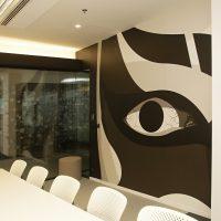 Matná černobílá fototapeta s geometrickým motivem oka nalepená na stěně zasedací místnosti, roh konferenčního stolu, bílé židle, skleněná příčka polepená řezanou pískovanou folií s motivem souhvězdí