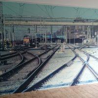 Wallwrap fototapeta potištěná fotografií vlakového nádraží a kolejí, nalepená na zdi, béžová podlaha