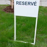 Bílá cedule s nápisem RESERVÉ v zelené trávě, mladá borovice s dřevěnou oporou, červeno-bílá páska, cihlově červená budova