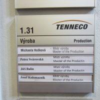 Zásuvný orientační systém s logem TENNECO, nápisem Výroba a označením pracovníků, přišroubovaný na strukturované zdi
