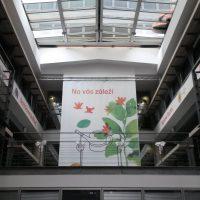 interiér budovy, nahoře prosklený strop, vpravo i vlevo schody do patra, po bocích na patrech nápisy, v pozadí visí ze stropu velký bílý banner