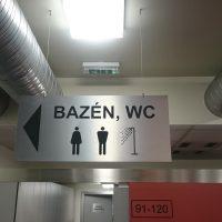 Závěsná stříbrná tabule s černým označením BAZÉN, WC, přišroubovaná na stropě, ventilační potrubí