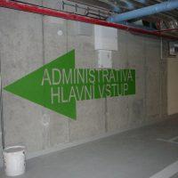 Zelená šipka doleva s vyřezaným nápisem ADMINISTRATIVA HLAVNÍ VSTUP, malovaná grafika na zdi jako značení uvnitř garáže, potrubí na stropě, na zemi bílý kbelík