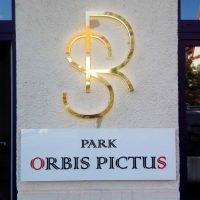 Sloup se světlou fasádou a bílým cihlovým obložením v dolní části, nad obložením bílý obdélník s černo-červeným nápisem, nad bílým obdélníkem zlaté logo tvaru písmen R a S, vlevo i vpravo černá okna