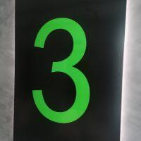 Černá podsvětlená deska označená světle zelenou číslovkou 3, přimontovaná na šedé zdi
