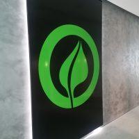 Černá podsvětlená deska označená zeleným logem ve tvaru lístku v kruhu, připevněná na šedé zdi chodby od stropu k podlaze